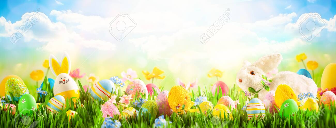 Easter eggs, bunny and spring flowers on meadow. Easter concept. Spring or summer background with fresh grass on blue sky backdrop with copy space. - 140025353