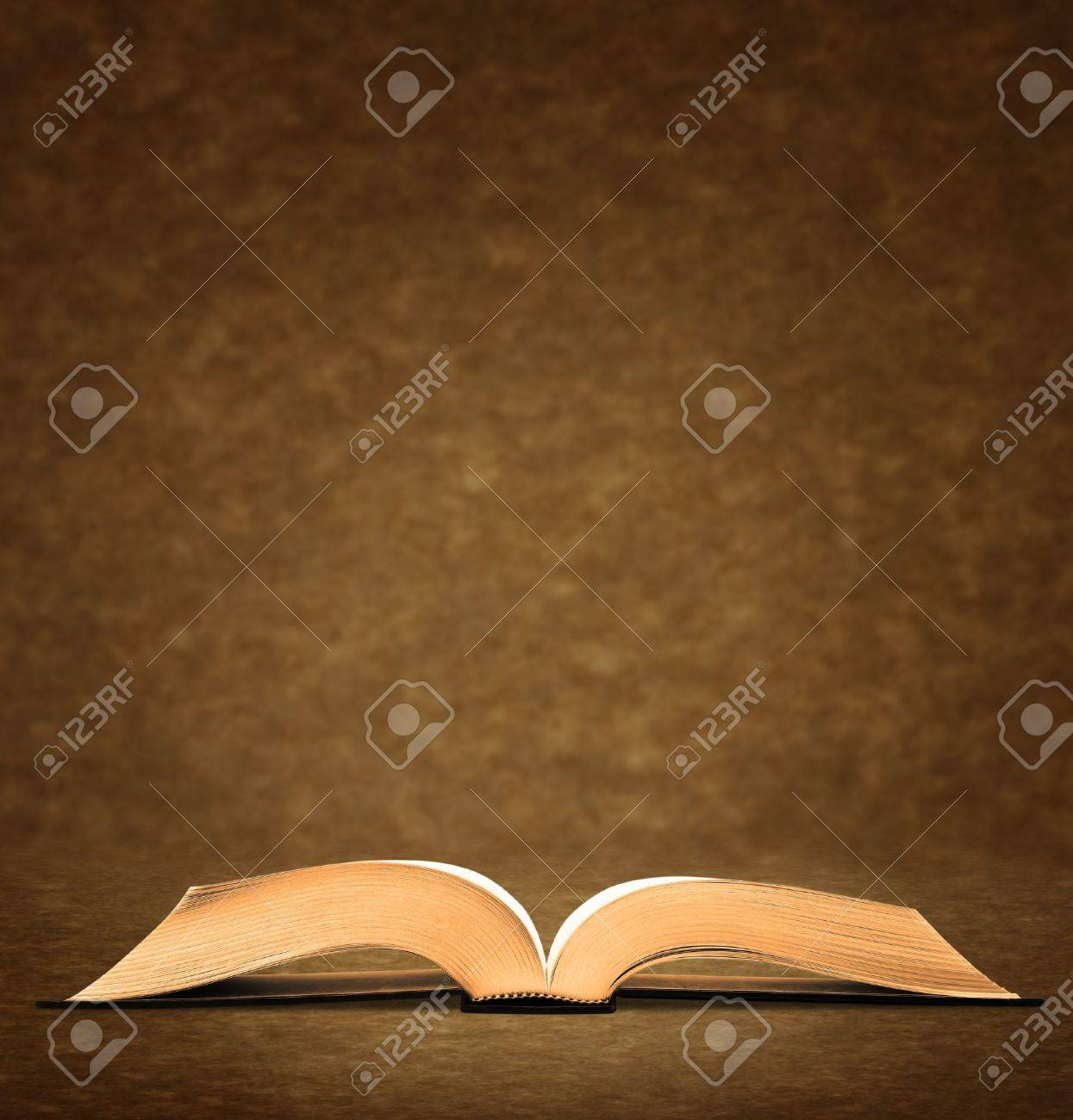 Open old book on brown background. Stock Photo - 10017125