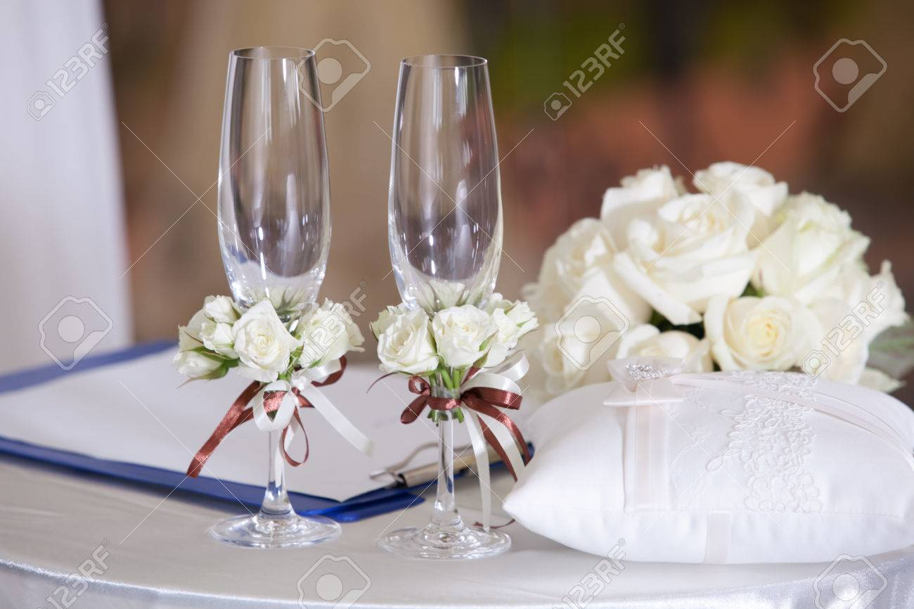 pair of wedding wineglasses on the table with flowers stock photo