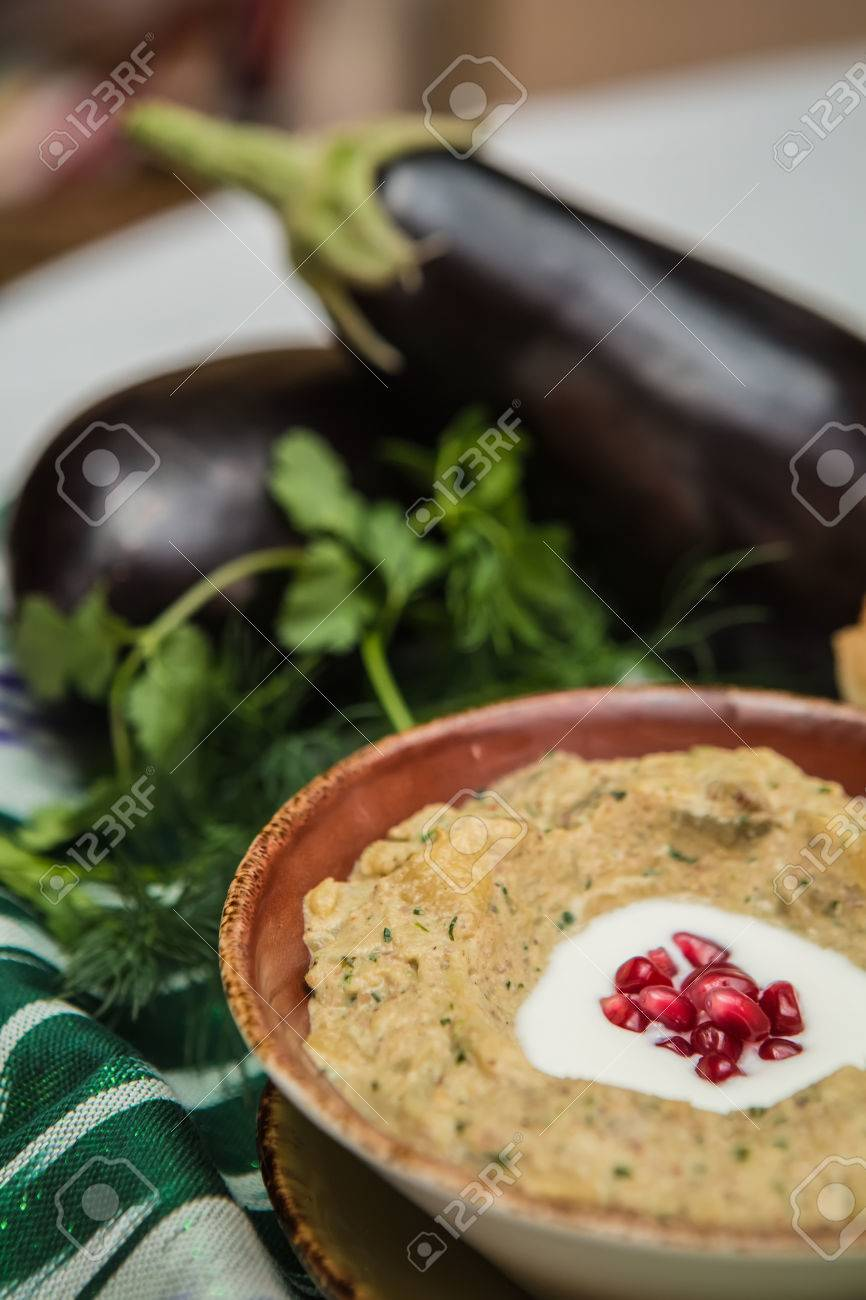 Traditional arabian eggplant dip baba ganoush with herbs and smoked paprika on a wooden background Standard-Bild - 38411618