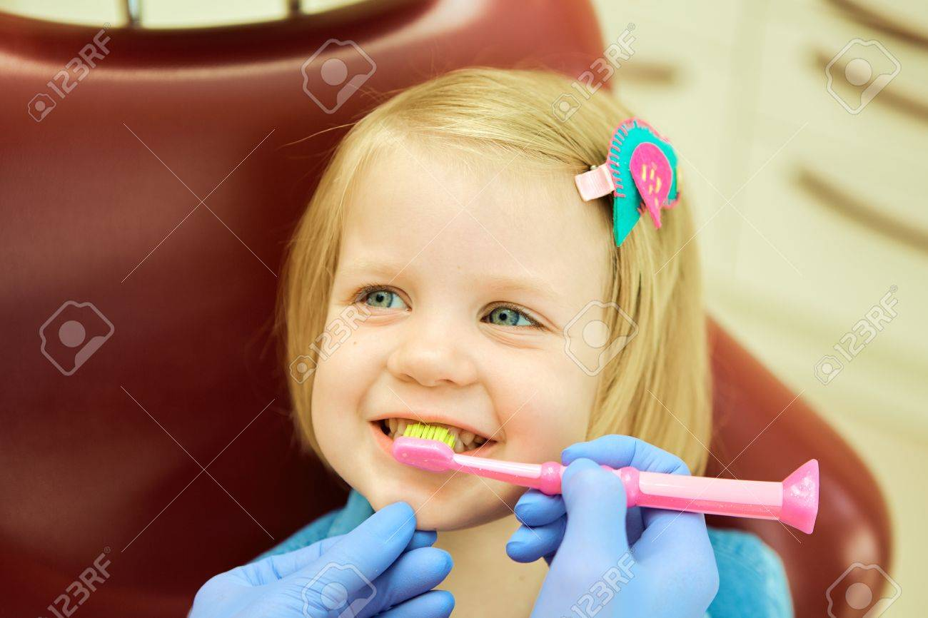 Little girl sitting in the dentists office. The dentist brushes teeth to the little girl Standard-Bild - 45990116