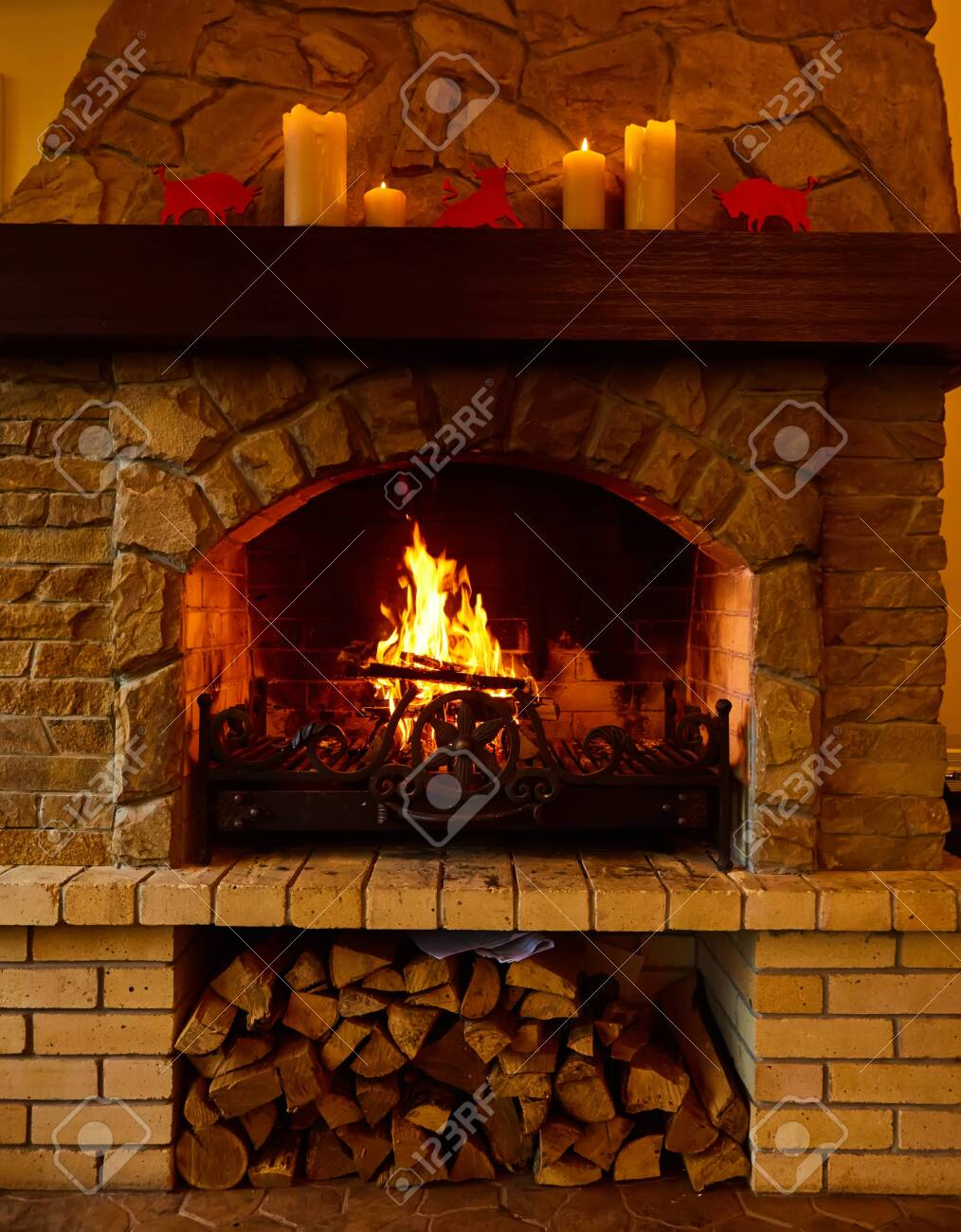 Warm cozy fireplace with real wood burning in it. Cozy winter concept. Christmas and travel background with space for your text. - 157441421