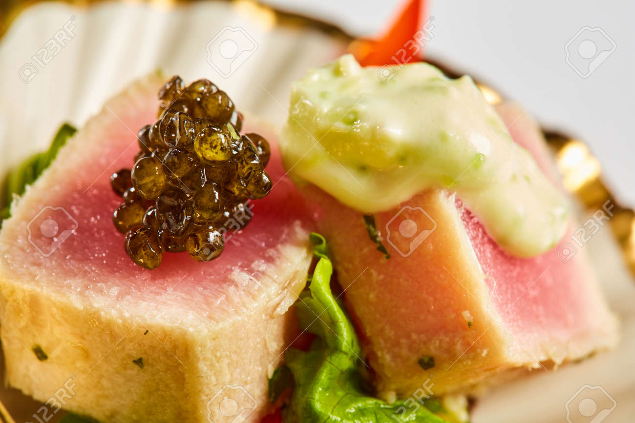 Close up of rare seared Ahi tuna slices with fresh vegetable salad on a plate. Shallow dof - 165938759