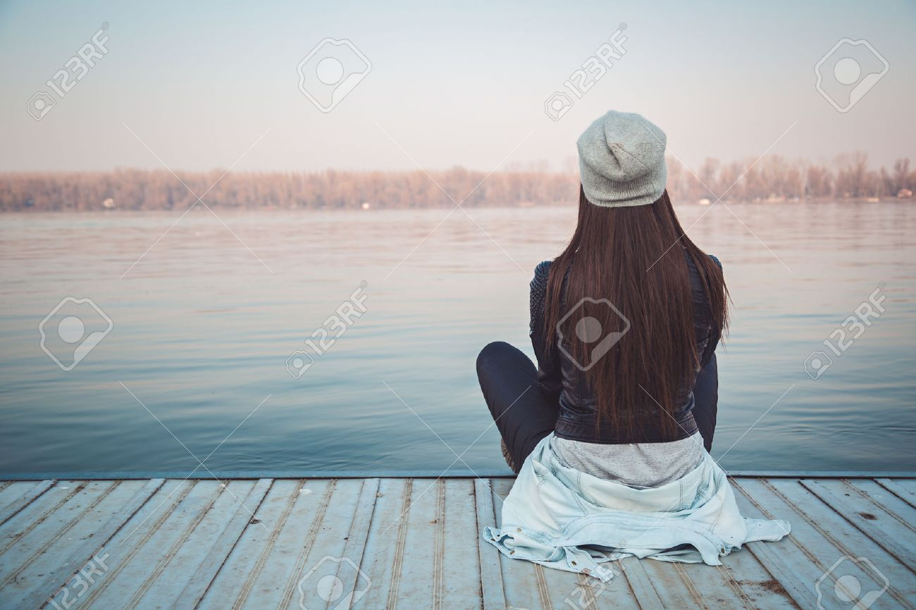 Girl sitting on pier and lookingat the river - 40838941