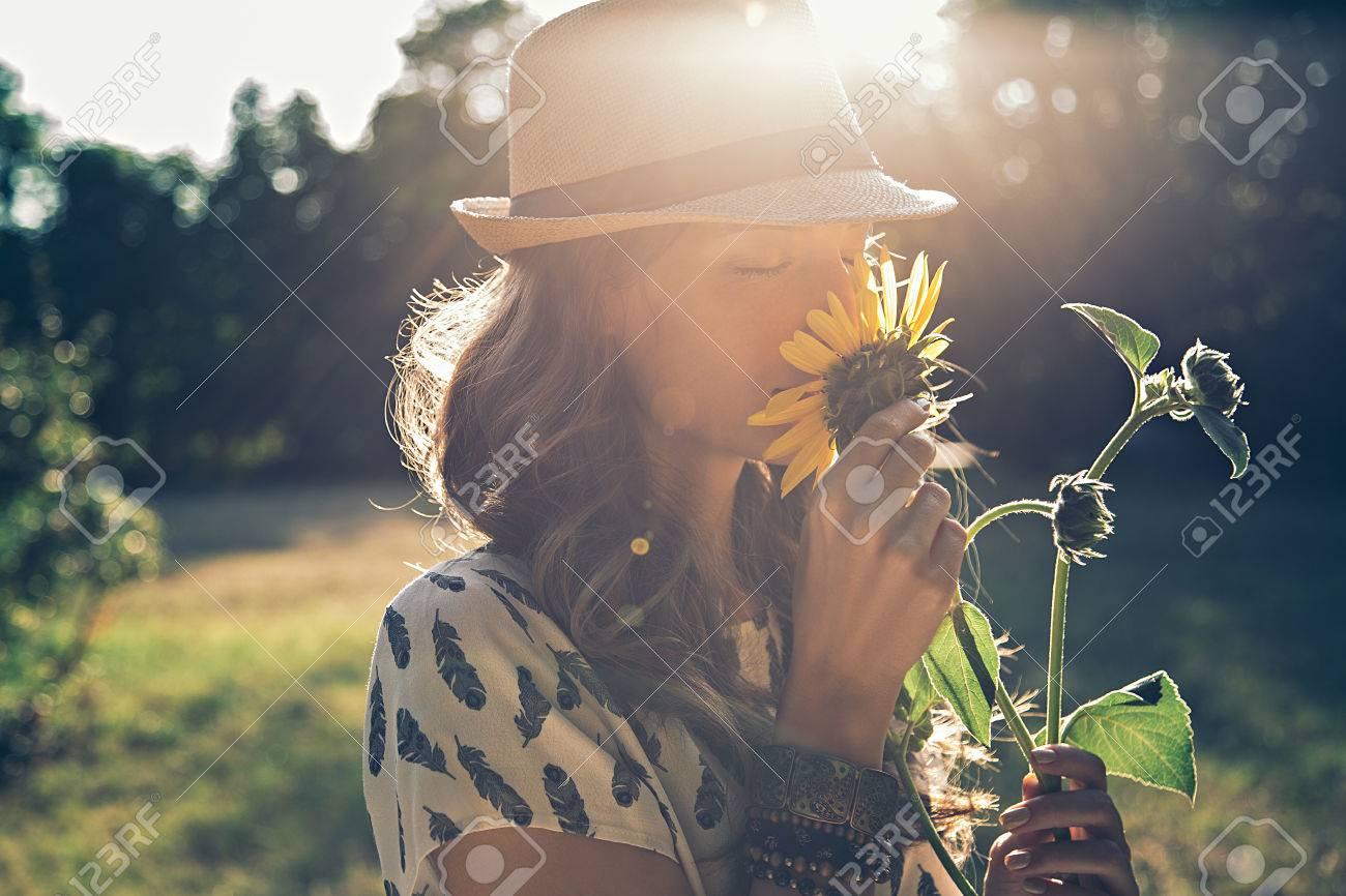 Girl smells sunflower in nature - 54033908