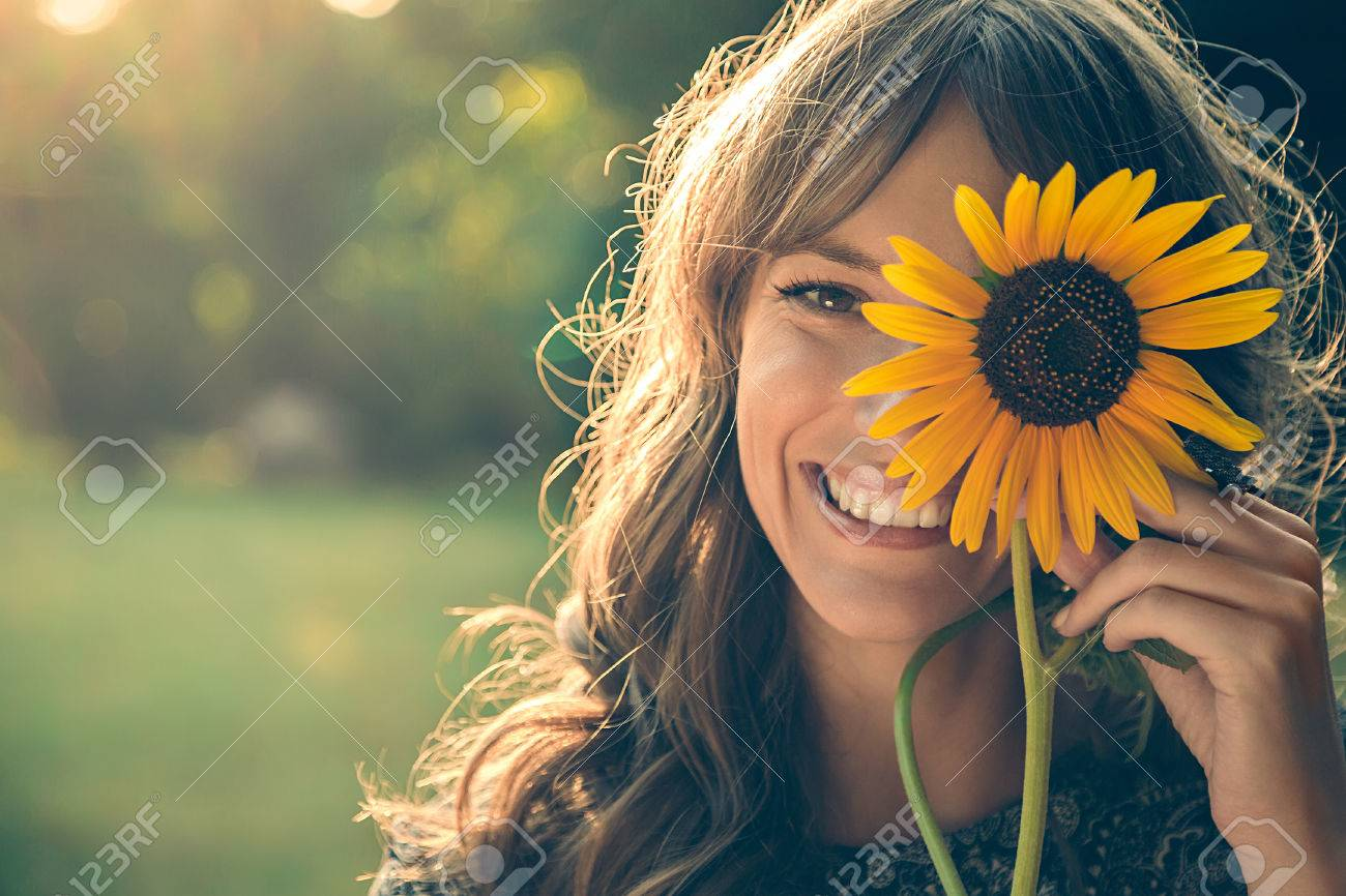 Girl in park smiling and covering face with sunflower Stock Photo - 54033405