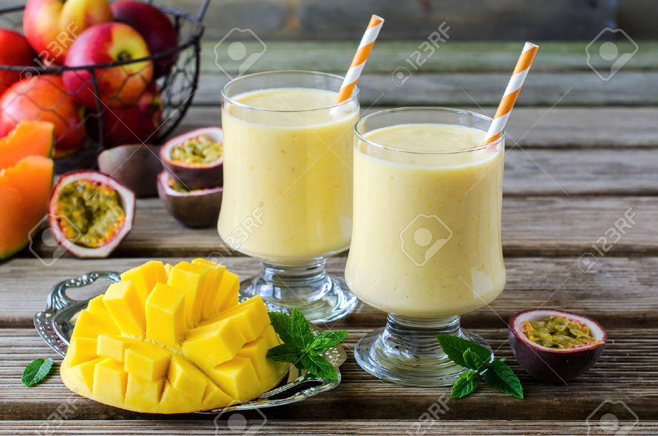 Healthy vitamin tropical mango and passion fruit smoothie with yogurt milkshake two glasses on wooden background - 41905832