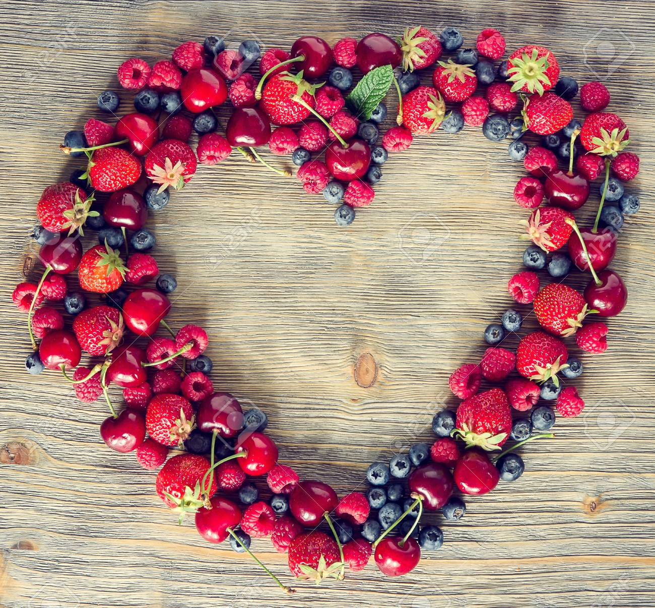 Fresh ripe berries, cherries, raspberries, blueberries lots of copy space, wooden background, summer fruits, harvest concept, vitamins food, heart shaped, square toned image - 41906000