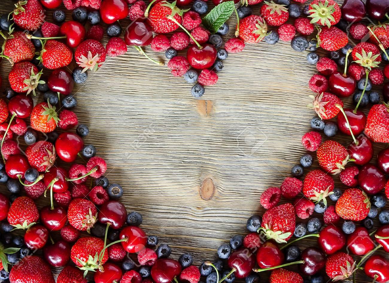 Fresh ripe berries, cherries, raspberries, blueberries copy space background, summer fruits, harvest concept, vitamins food, heart shaped - 41906003