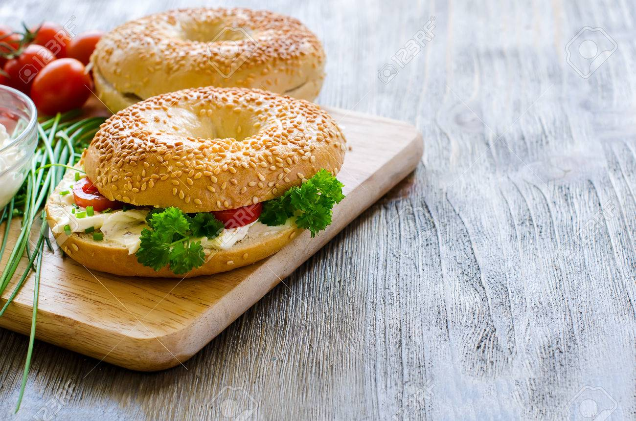 Bagels sandwiches wtih cream cheese, tomatoes and chives for healthy snack - 42640820