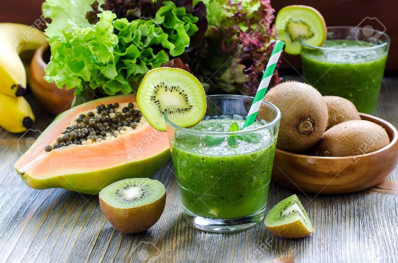 Green healthy kiwi tropical fruits smoothie with papaya and bananas - 42642436