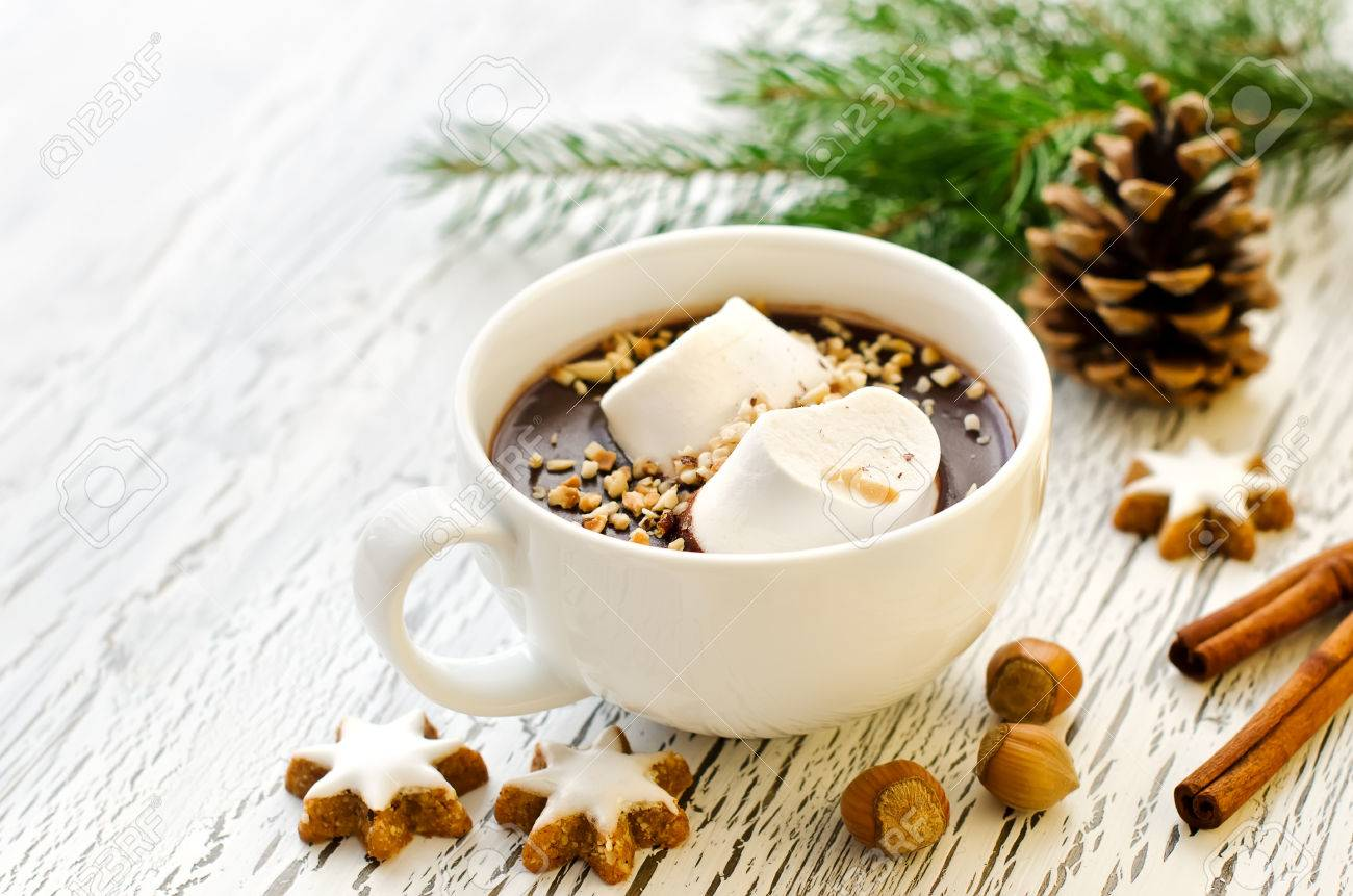Hot winter beverage with nuts on white wooden background - 47416399