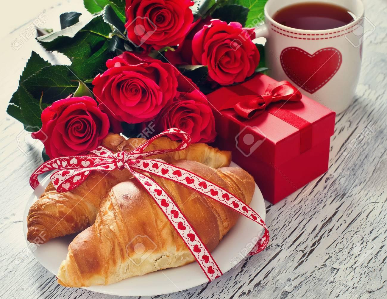 Desayuno romántico con té en tazas, cruasanes, caja de regalo y rosa Foto de archivo - 52523337