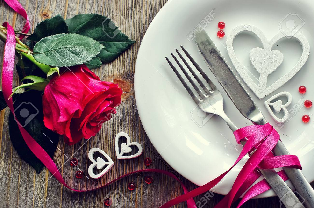 Romantic dinner with rose, tableware and hearts on wooden background - 52523333