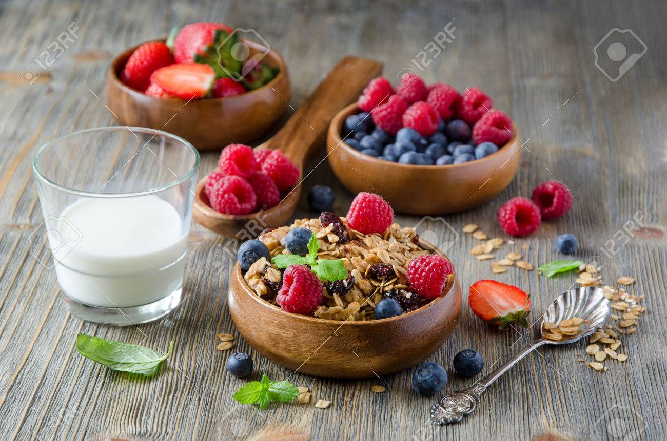 Breakfast with rolled oats and berries in wooden bowls - 54942646