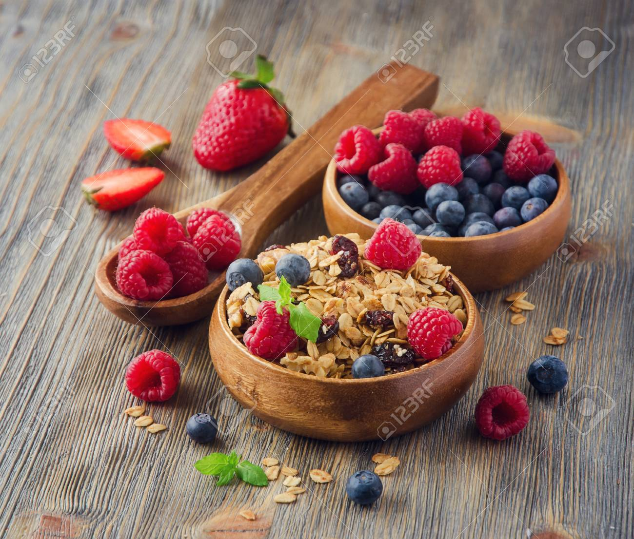 Healthy reakfast with rolled oats and berries in wooden bowls, rustic background, square image - 54942648