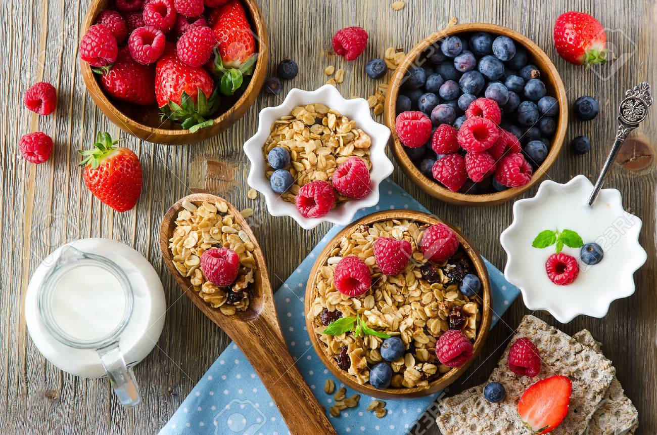 Healthy breakfast, muesli, raspberries, blueberries, strawberries, crisp bread and yogurt, health and diet concept - 54942662