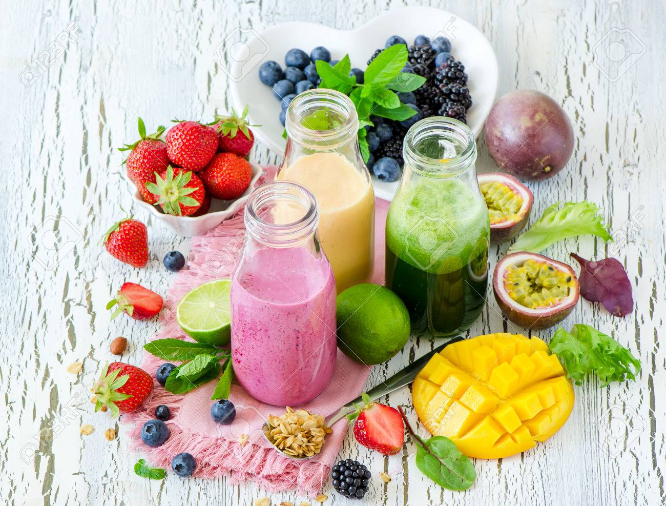 Berry and fruit smoothie in bottles, healthy summer detox yogurt drink, diet or vegan food concept, fresh vitamins, mango, lime, passtion fruits - 60675062
