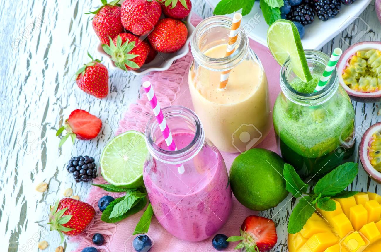 Berry and fruit smoothie in bottles, healthy summer detox yogurt drink, diet or vegan food concept, fresh vitamins, mango, lime, passtion fruits - 60638841