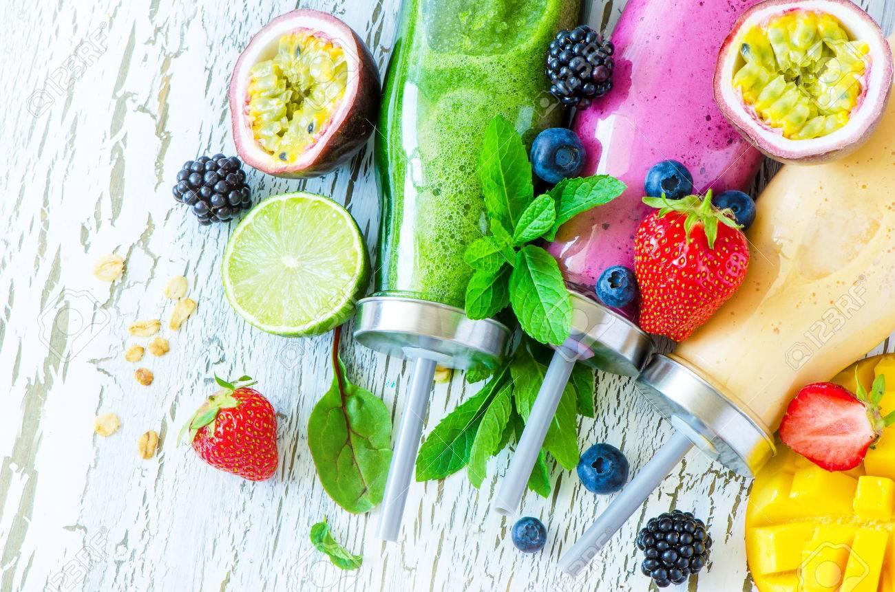 Berry and fruit smoothie in bottles, healthy summer detox yogurt drink, diet or vegan food concept, fresh vitamins, mango, lime - 60638845
