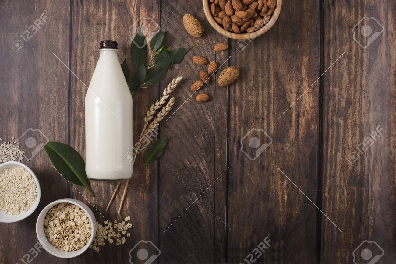 Plant based milk alternative in bottle on wooden background, ingredients for plant milk, almond, oat, rice milk, flat lay, copy space for text - 142635259