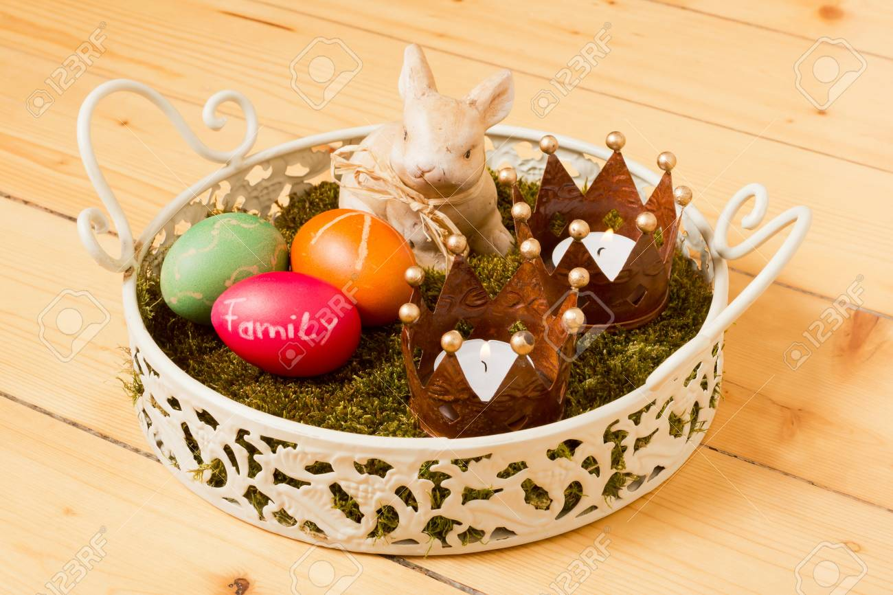Easter basket with moss colorful eggs a bunny and two burning tealights in front of a wooden background Stock Photo - 13165675