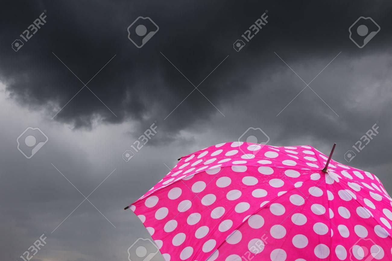 A pink umbrella in front of dark rain clouds Stock Photo - 13868220