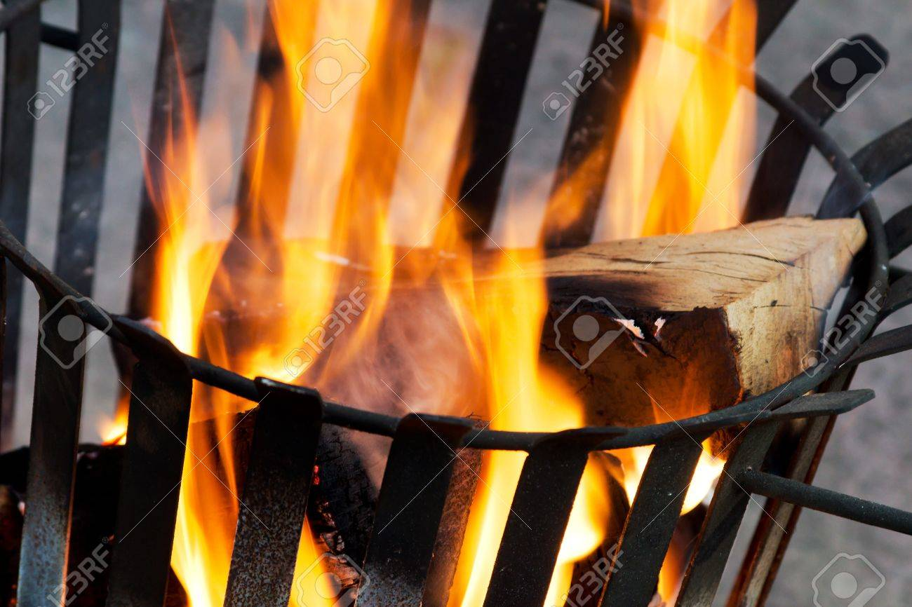 Closeup of an old rusty fire basket with burning wood Stock Photo - 13946897
