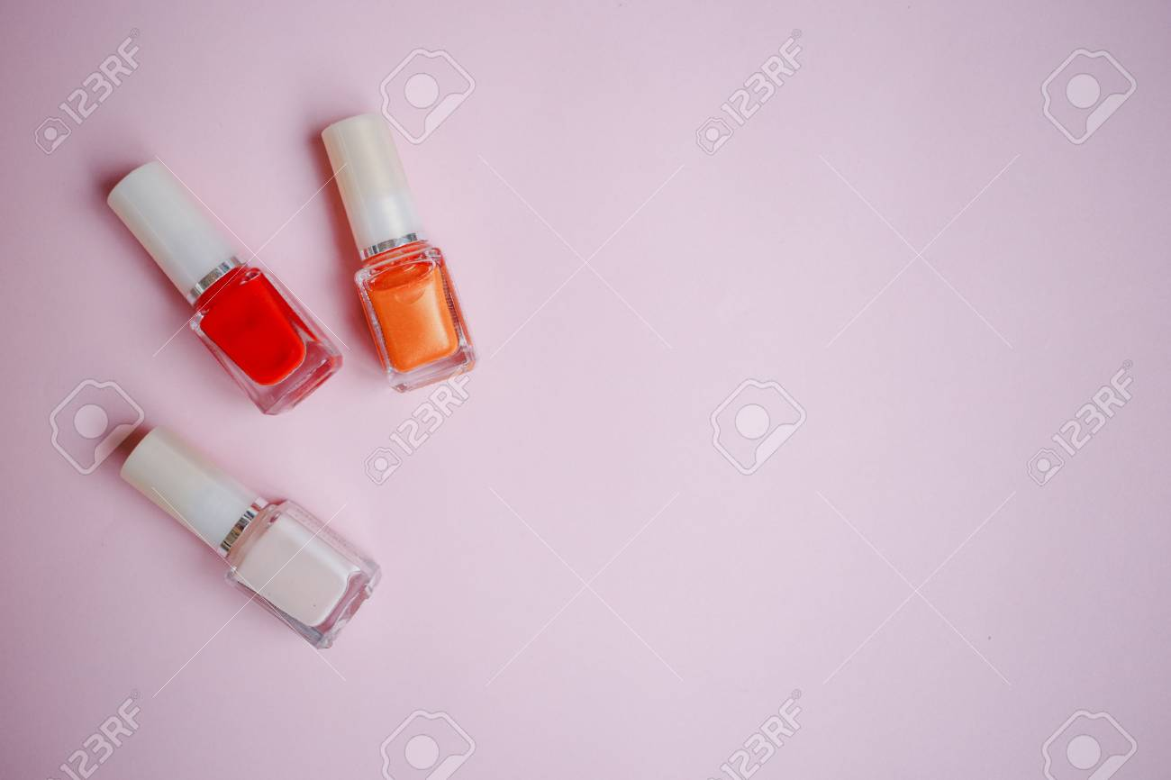 Multi-colored Nail Polishes On Pastel Pink Background, Top View ...
