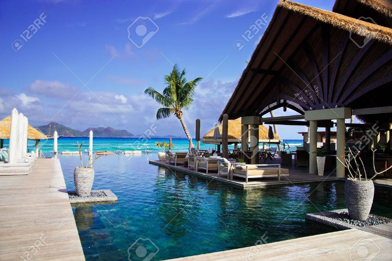 swimming pool and loung area with tiki hut in luxury hotel in seychelles stock photo - Tiki Hut