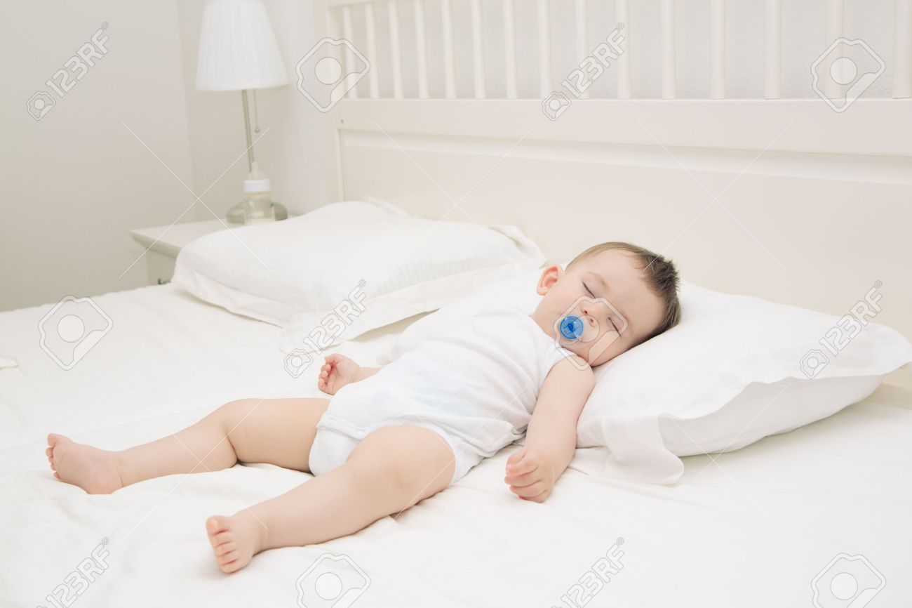 Adorable baby sleeping relaxed and sprawl in parent's bed Stock Photo - 20411547