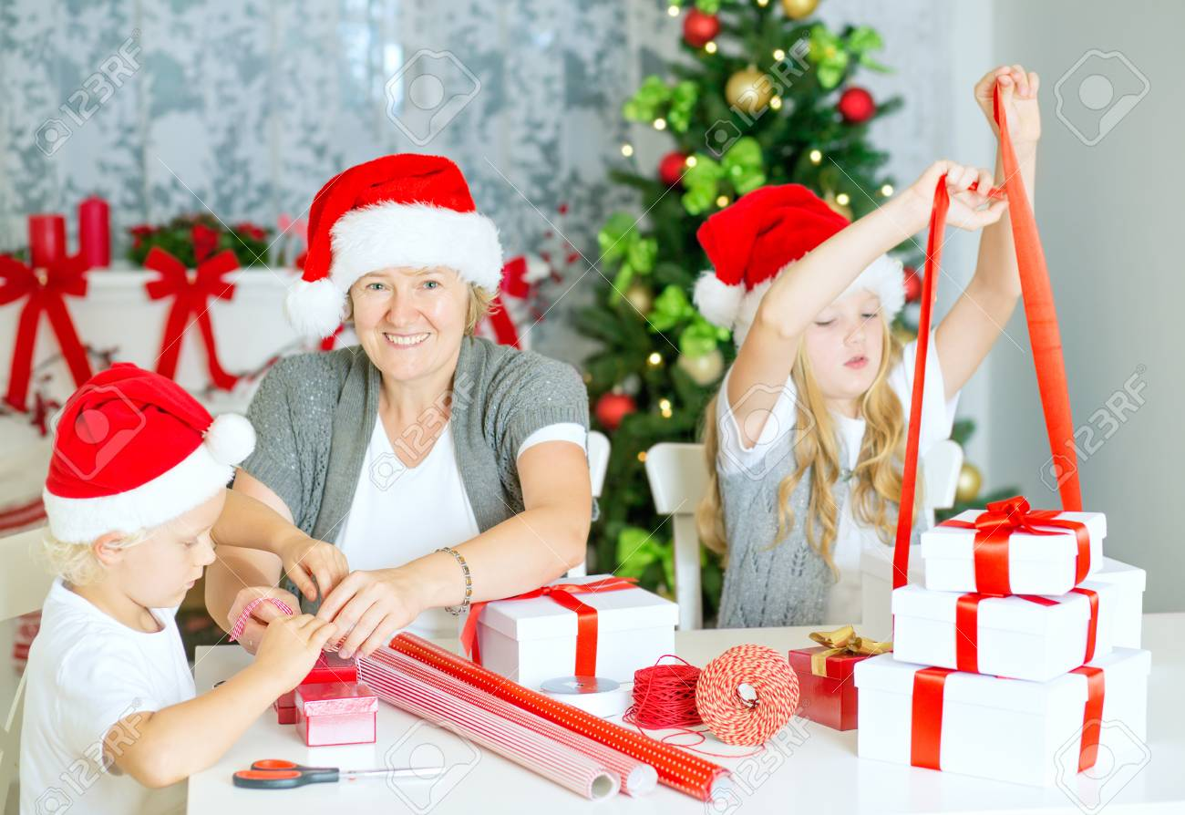 Happy Family Of Three, Mom With Children Wrapping Christmas Gifts ...