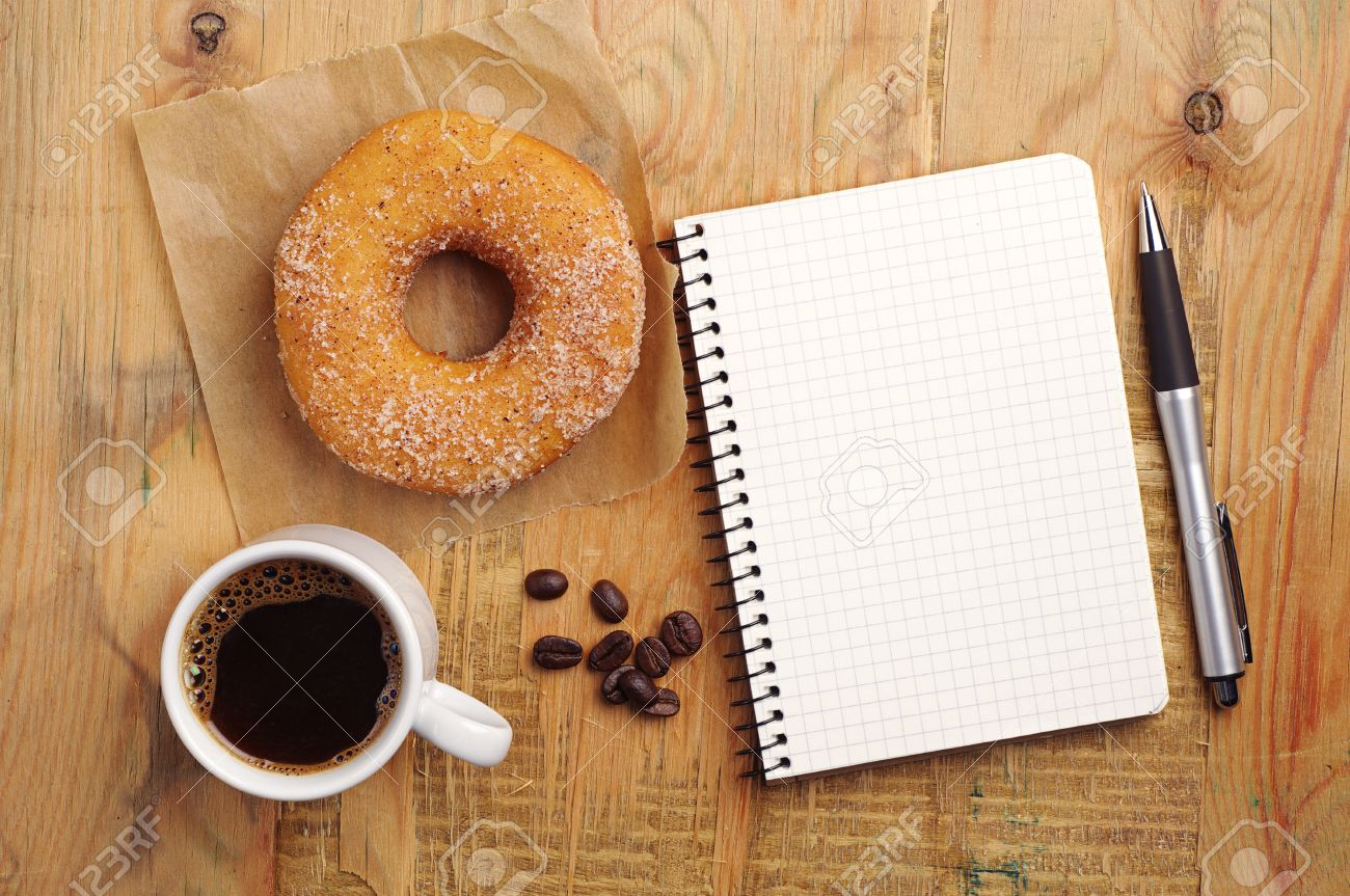 Opened Notebook And Cup Of Coffee With Donut On Wooden Desk ...