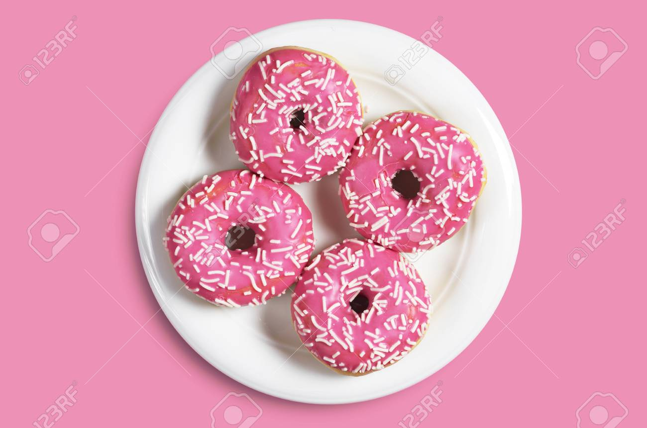 Small donuts with sprinkles in white plate on pink background,