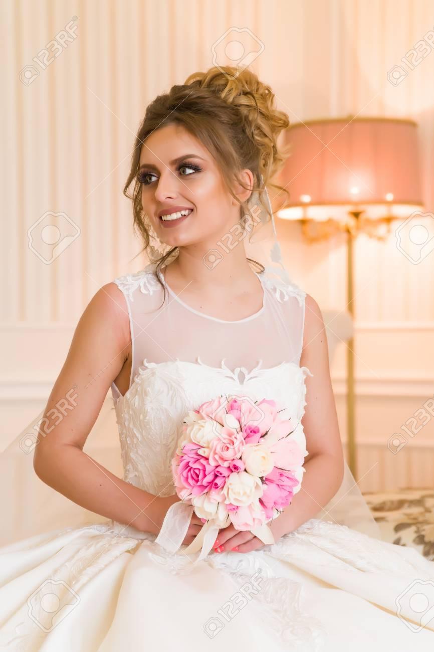 8052ca3ad858 Archivio Fotografico - Ritratto di bella giovane sposa. Una ragazza sta  posando in una stanza d albergo. Una signora è seduta con un mazzo di rose  vicino ...