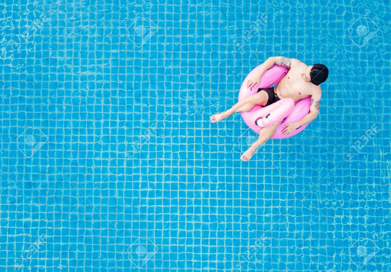 Top view, a man relaxing on pink flamingo swim pool float, on..