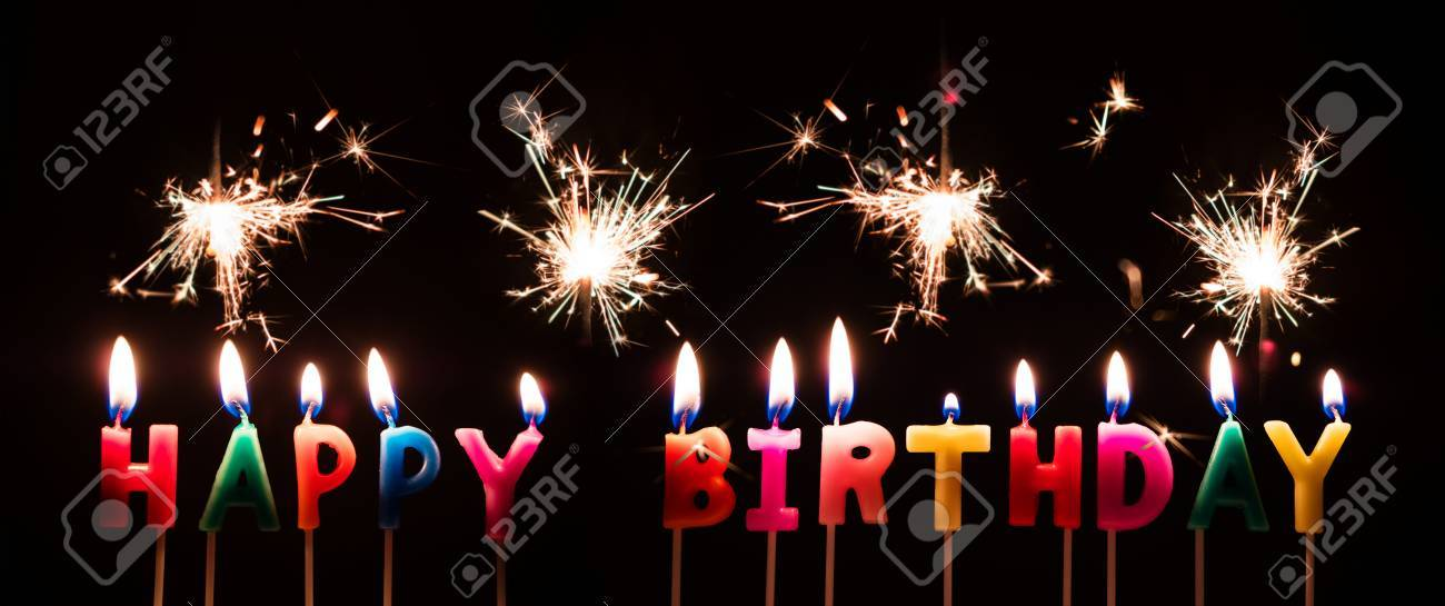 Colorful Happy Birthday Candles With Sparkler Fireworks On Black Background Stock Photo