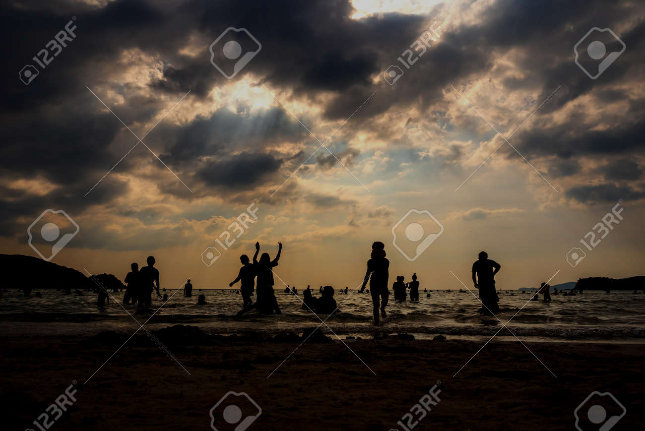 Silhouette in the evening light of people playing in the sea at a public beach - 167263235