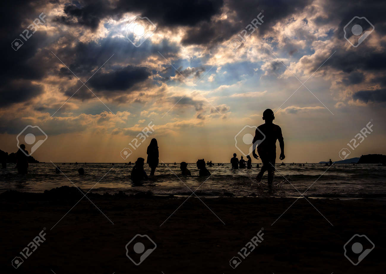 Silhouette in the evening light of people playing in the sea at a public beach - 167263637