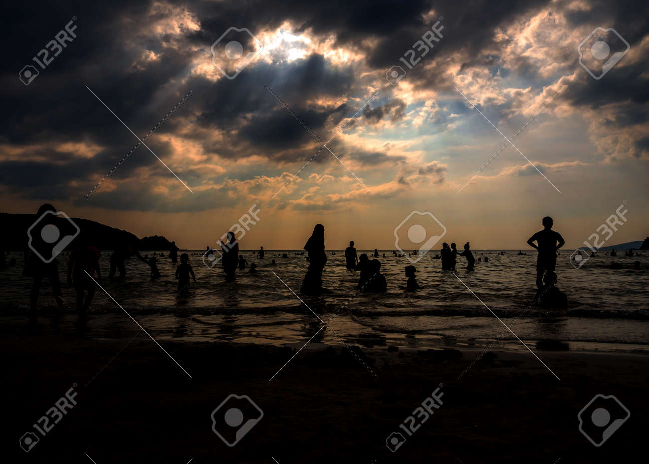 Silhouette in the evening light of people playing in the sea at a public beach - 167263891