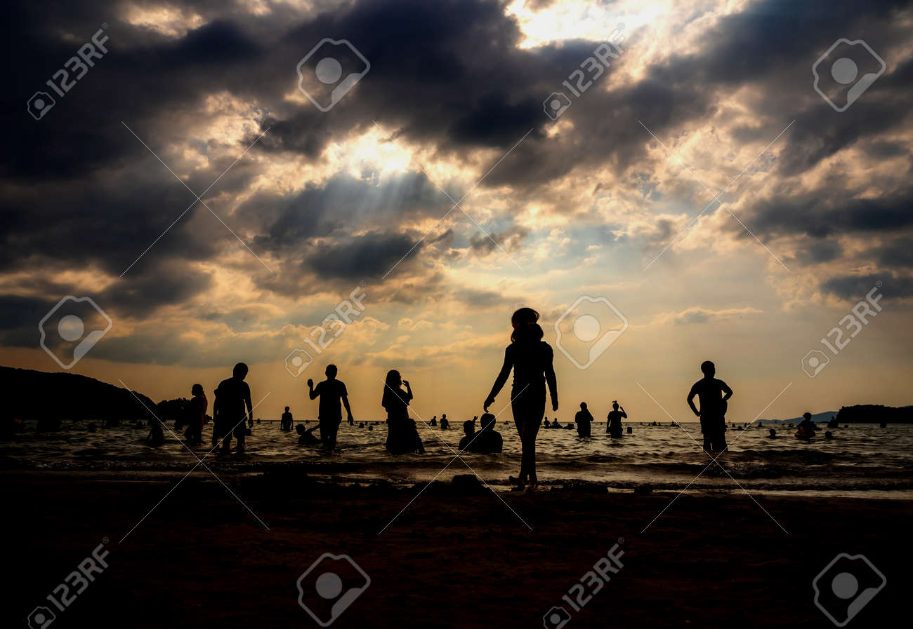 Silhouette in the evening light of people playing in the sea at a public beach - 172429615