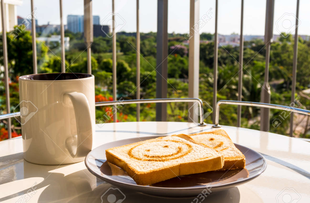 The cup of coffee and some bread breakfast with morning light at the balcony - 172430190