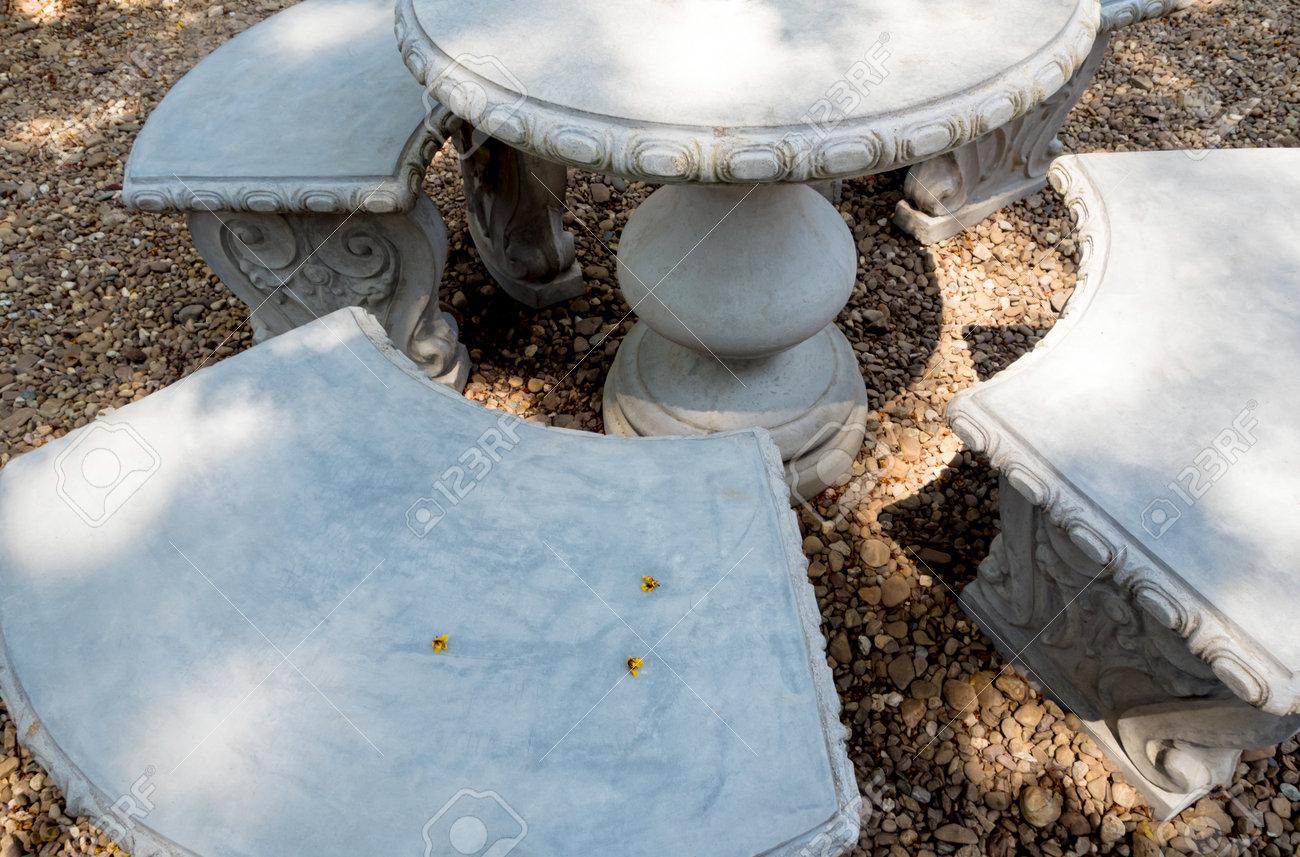 Stucco outdoor table set on the gravel floor in the garden - 170317595