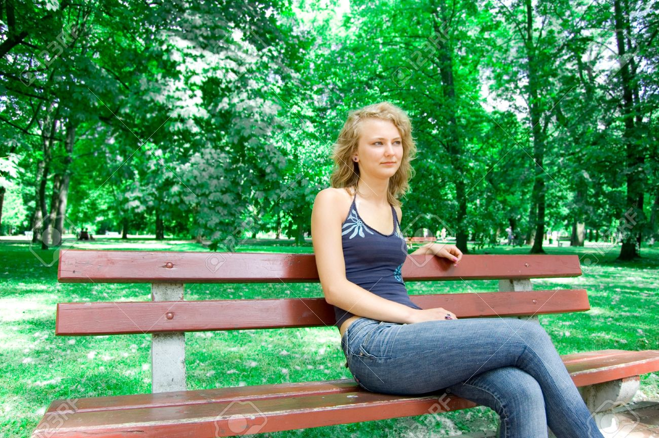 Young Beautiful Girl Sitting On A Park Bench Stock Photo Picture