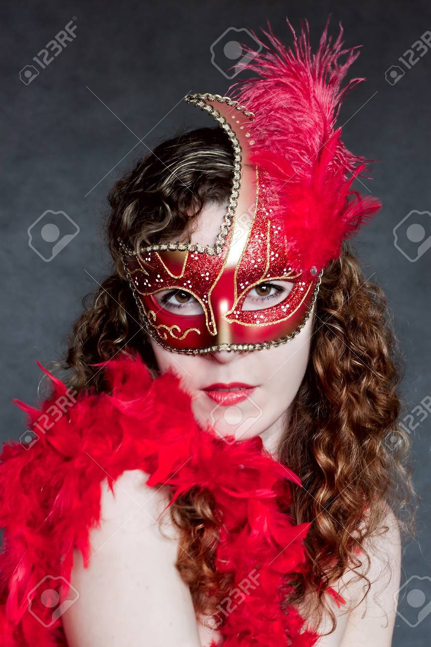 Beautiful young lady in a red venetian mask Stock Photo - 12776231