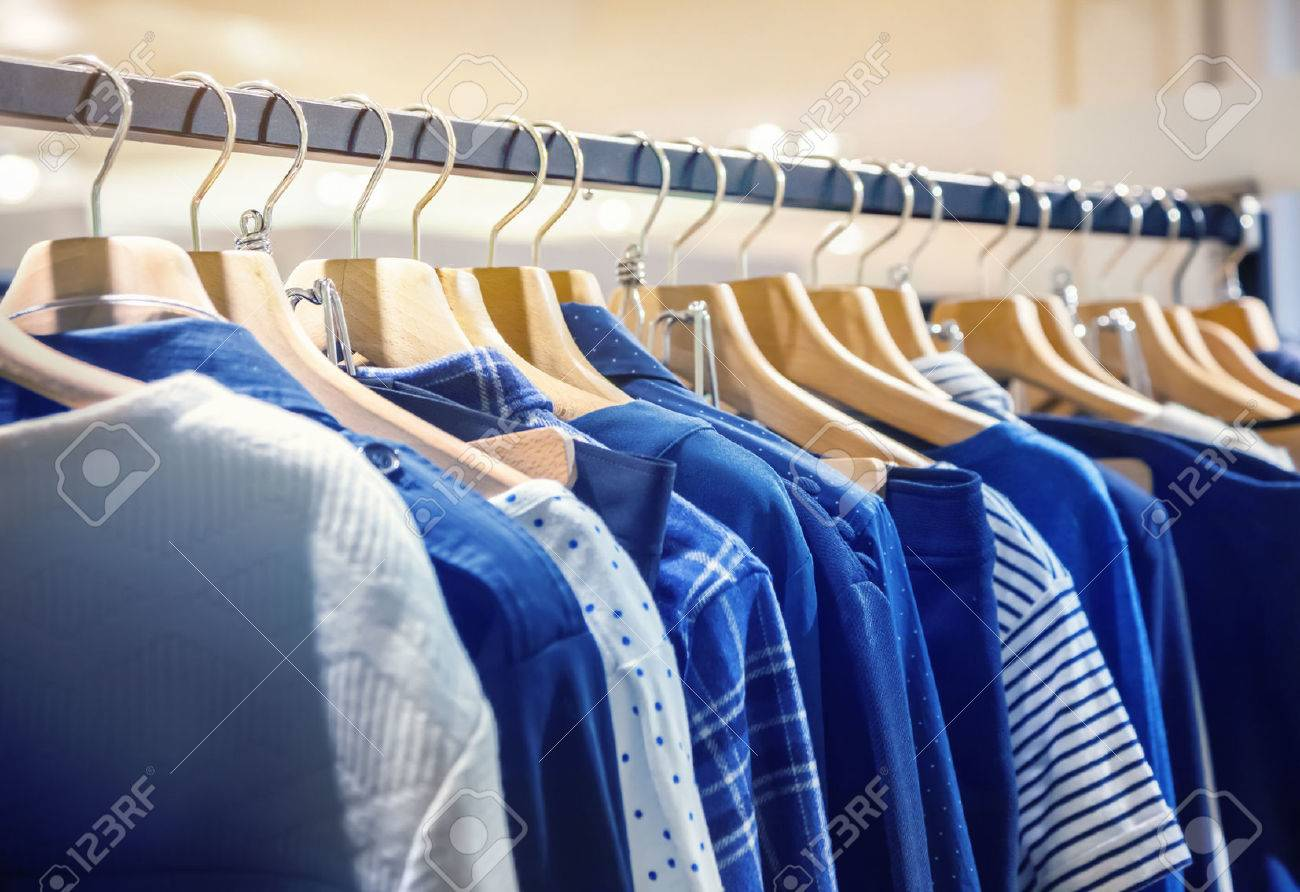 A row of clothes hanging on the rack - 48449337