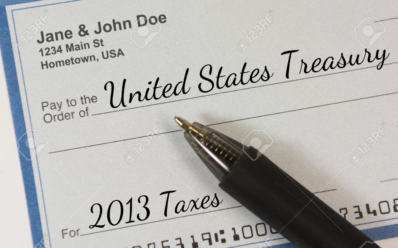 A personal check with pen, made payable to the United States Treasury for 2013 Taxes Stock Photo - 25347051