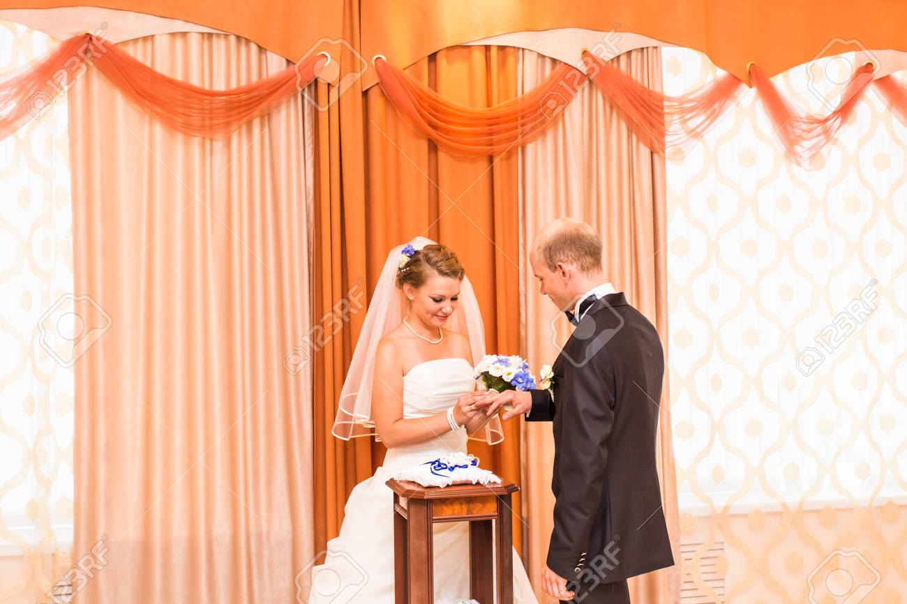 Bride putting a ring on groom's finger during wedding ceremony. - 50311599