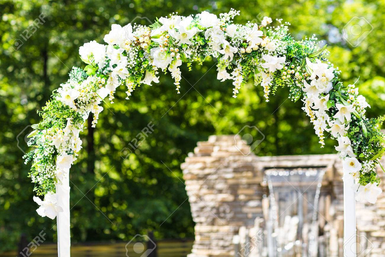 Beautiful White Wedding Arch Decorated With White Flowers Outdoors