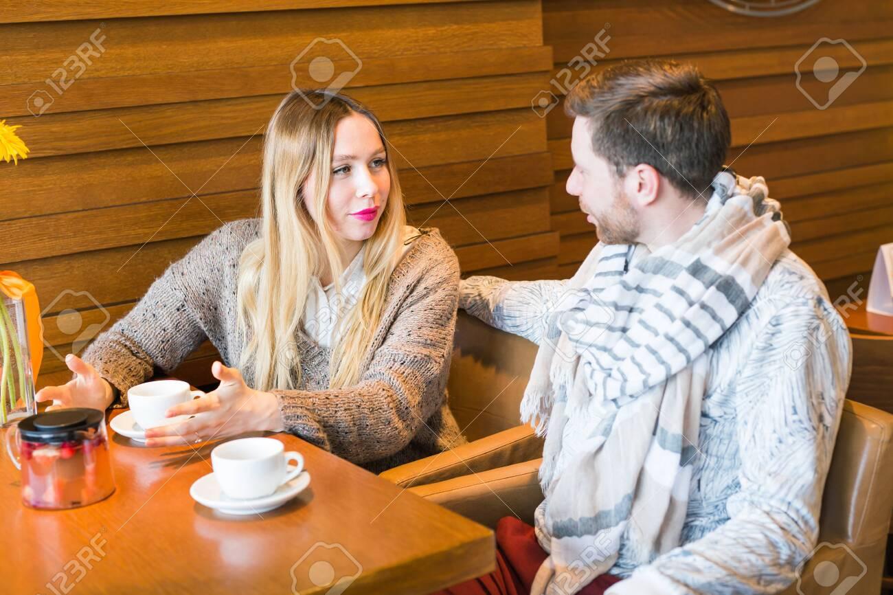 Immagini Stock La Donna Parla Con L Uomo Seduto Al Tavolo Al Caffe Image 60416783